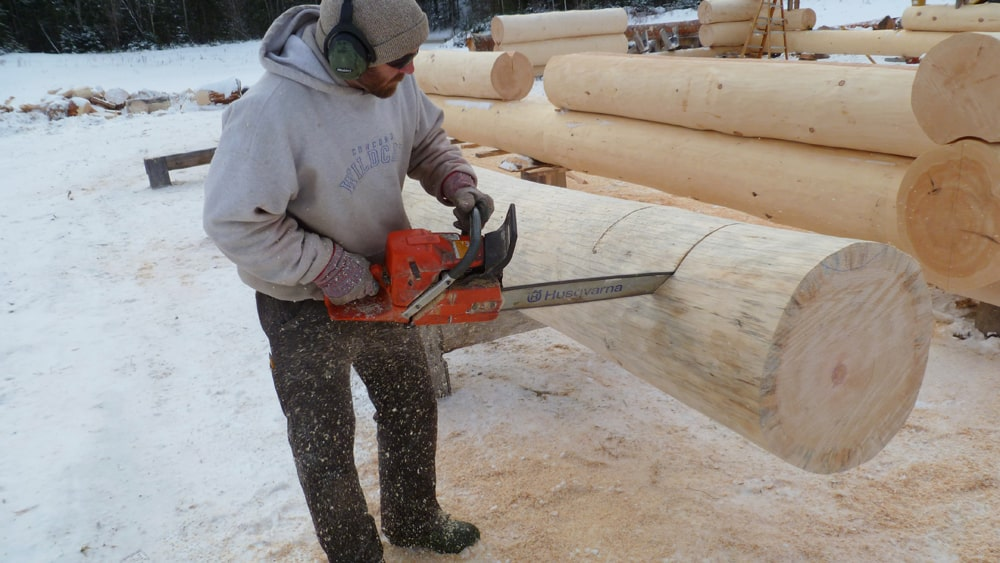 Log cabin builder using chainsaw to cut saddle notch