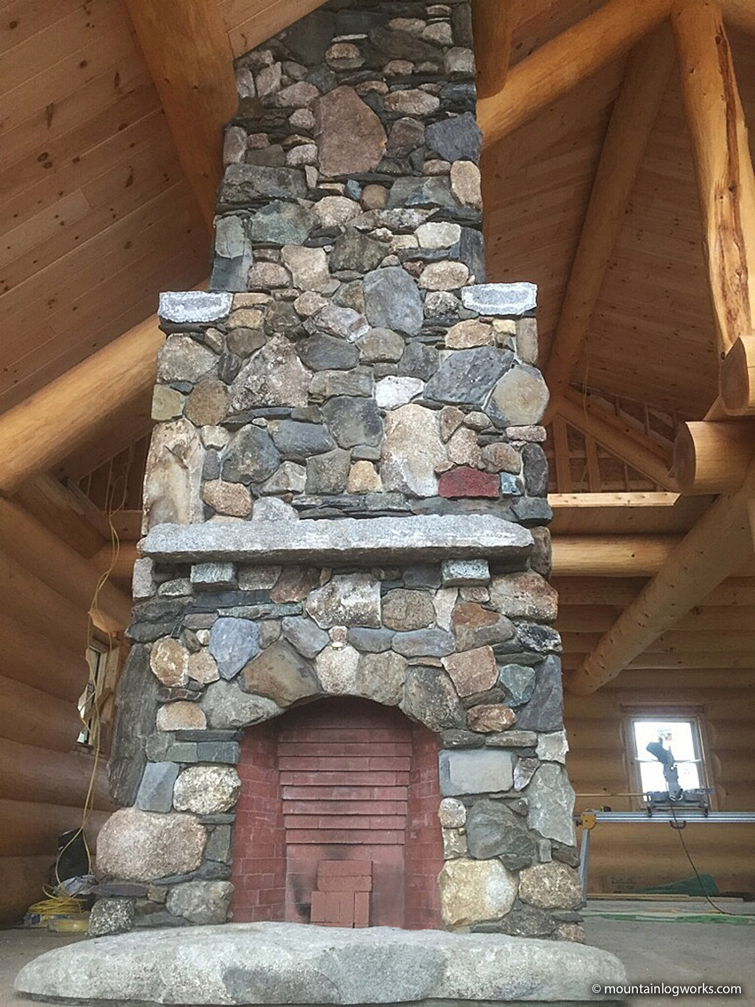 Stone fireplace construction in log cabin