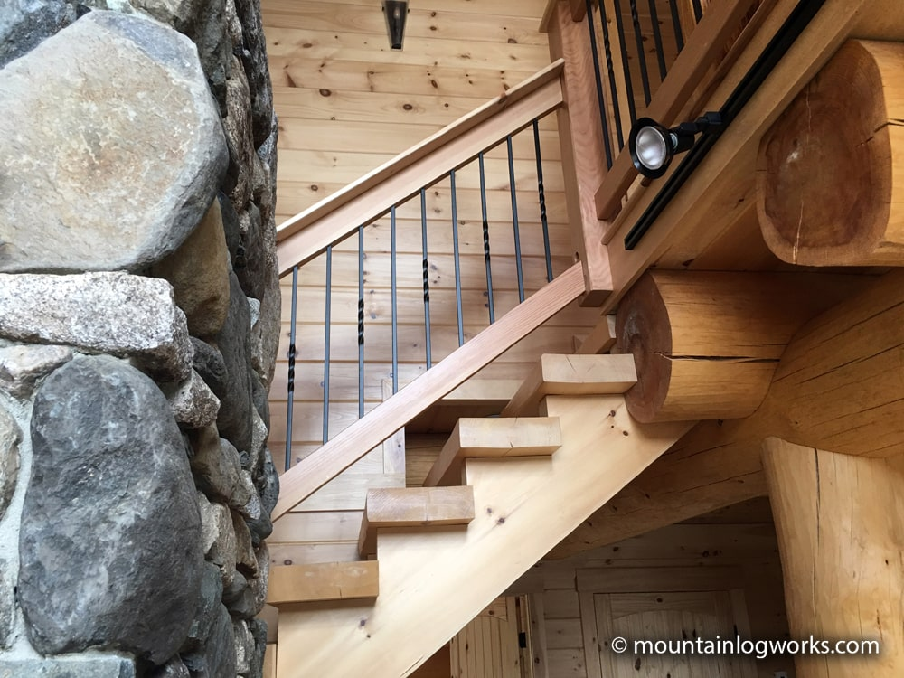 Log cabin stairs next to stone fireplace