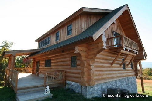 Log cabin home with stone foundation, porch, and balcony