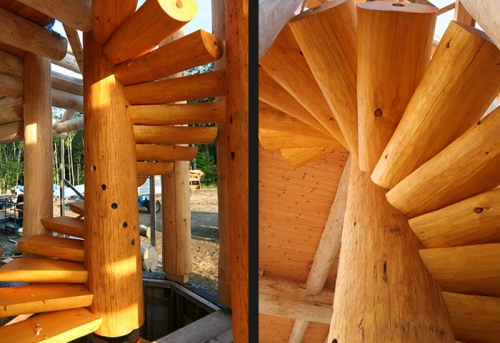 Custom spiral log stairs in cozy log cabin